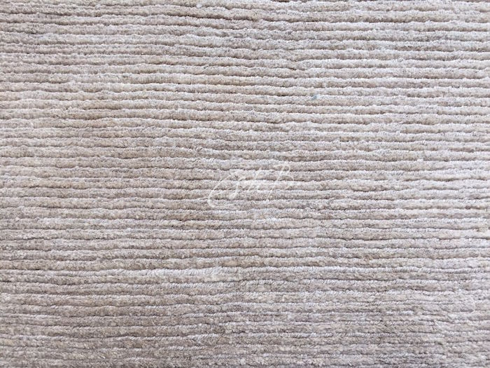 closeup of hand-knotted rug made from linen, in neutral colour