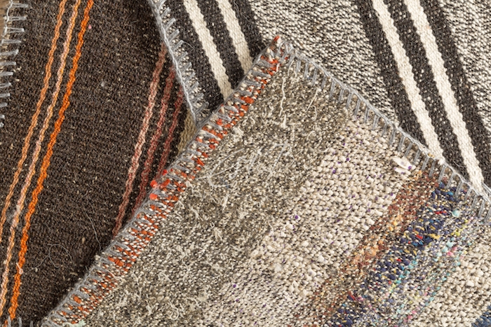 close-up of three kilims in shades of brown and taupe with striped patterns